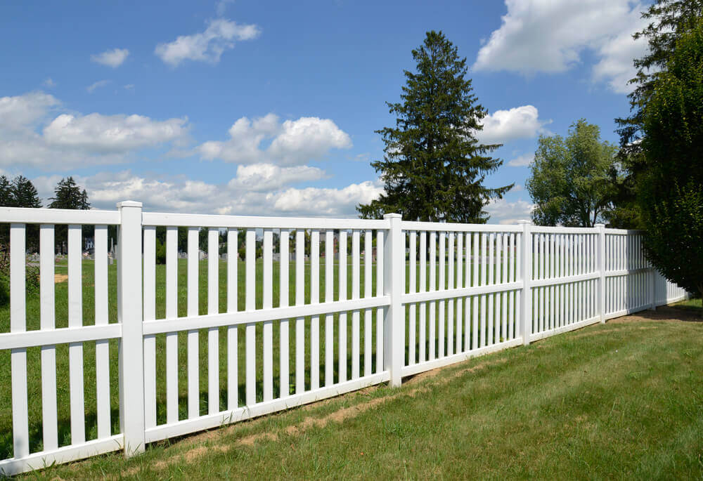 image of a white aluminum fencing panels with nice green grass either side and a tree to the right