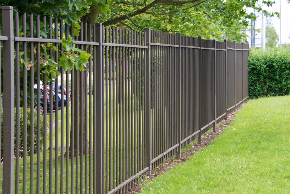 a standard black vertical steel bar fencing panels in a park with green grass everywhere