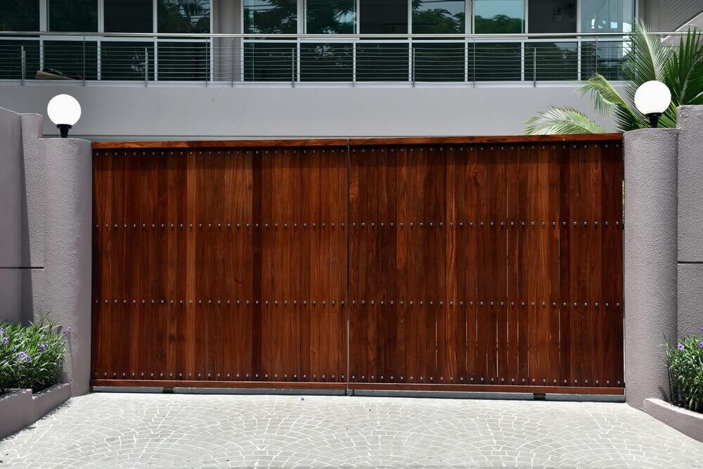 a large dark brown wooden automatic gate with rendered walls either side