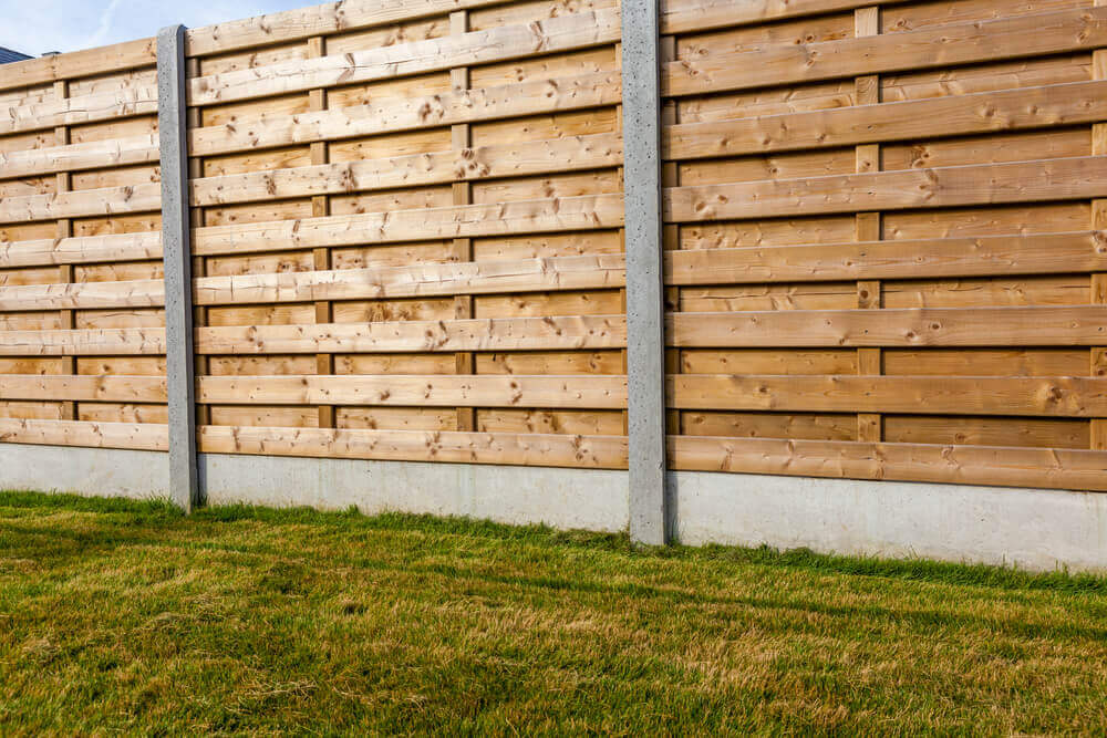 a large fence with horizontal wooden planks and steel vertical supports with a concrete footer made by fencing Ballarat